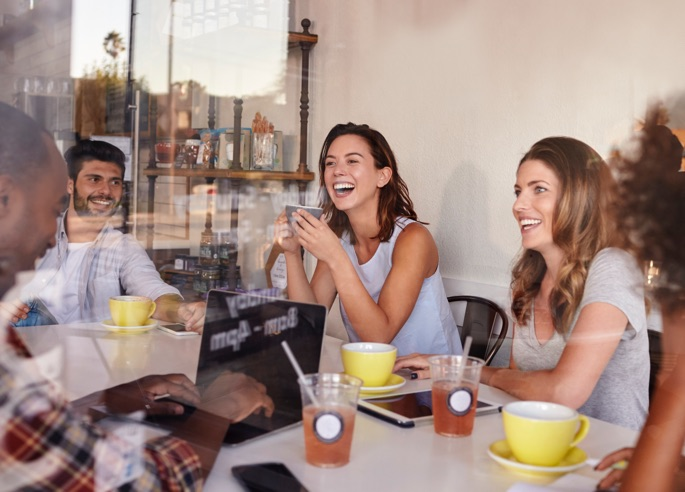 Group of young people smiling at a cafe